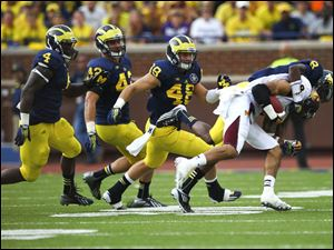 Central Michigan's Winslow Chapman (8) is tackled by Michigan's Channing Stribling (8).
