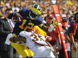 Michigan's Devin Gardner (12) is tackled out of bounds by Central Michigan's Brandon Greer (35).