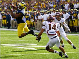 Michigan's Jeremy Gallon catches a pass in front of Central Michigan's Jason Wilson (14).