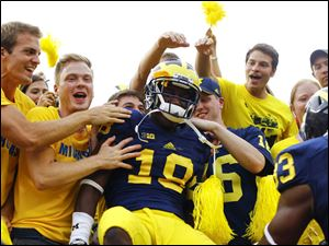 Michigan's DeAnthony Hardison celebrates with fans after the win.