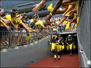 Michigan players take the field to practice before the game.