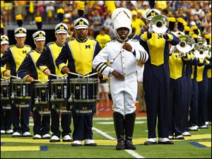 The Michigan Marching Band takes the field.