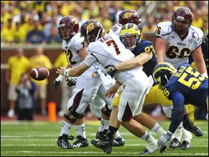 Michigan's Brennen Beyer (97) forces a fumble on Central Michigan quarterback Cody Kater (7) causing a turnover.