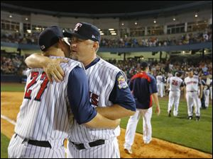 Toledo Mud Hens manager Phil Nevin gets a hug from Kenny Faulk after the Hens' win. Nevin was notified that his contract would not be renewed shortly after the game.