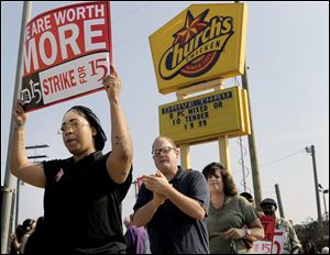 Taco Bell employee Shanise Stitt, left, pickets with other protestors in front of the Church's Chicken fast food restaurant Thursday in Detroit.