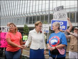 Carla Bachmayer, of Genoa, Rep. Marcy Kaptur (D-Oh), center, and Phyllis Coughenour, of Toledo, along the parade route. Bachmayer says she is a strong supporter of Kaptur, and wanted to express her position against war in Syria. Phyllis Coughenour is the widow of the recently deceased Ronald E. Coughenour, labor leader and past parade grand marshall, and spoke to Kaptur about her husband.