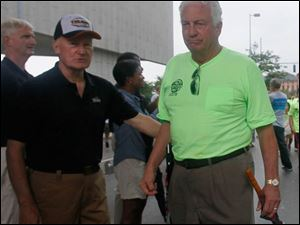 Former Toledo mayor Carty Finkbeiner, left, with Ron Rothenbuhler, chair of the Lucas County Democratic Party, right, as Rothenbuhler marches with other members of the carpenters' union.