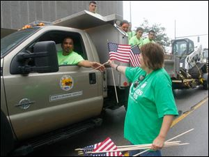 Mario Morena, with the City of Toledo Sewer and Drainage Services, left, receives a flag from Joan Pruss along Summit Street.