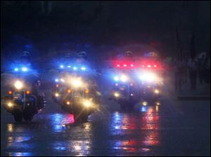 The motorcycle division of the Toledo Police Department starts the parade in a downpour.