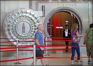 "Tourists pass the vault exhibit containing the ""secret recipe"" for Coca-Cola at the World of Coca-Cola museum in Atlanta. The 127-year-old recipe for Coke sits inside a steel vault that's bathed in red security lights, while security cameras monitor the area to ensure the formula stays a secret."
