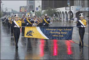 The Whitmer High School band marches through the rain near the front of the annual Labor Day parade in downtown Toledo.