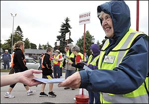 Gloria Reid of Washington, Mich., hands out certificates at the bridge walk. Prizes to to walkers with lucky numbers.