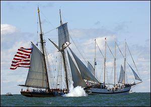 The Pride of Baltimore II, left, fires as it moves by the Windy during the re-enactment of the Battle of Lake Erie, a decisive confrontation of the War of 1812, near Put-in-Bay, Ohio.