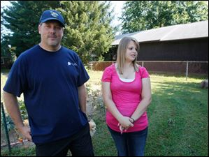 Rob Scott, left, and his 15-year-old daughter Ariel near their former pool and now garden.