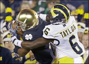 Notre Dame's TJ Jones makes a catch against Michigan's Raymon Taylor last season. Next year's contest could be the last for a while.