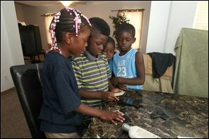 Cleo Wallace's children from left: Jhonye Wallace, 6, Jahmal Wallace, 8, JeBron Wallace, 5, and Jaymar Wallace, 7, play a game together while their mother finishes packing for their move to a place near Atlanta.