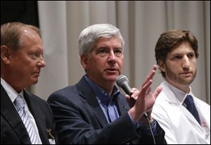 Gov. Rick Snyder, center, is expected to sign the measure which adds low-income residents to Medicaid coverage in Michigan.