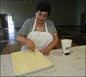 Olympia Ntakos, of Sylvania Township, one of the chairs, cuts the baklava and performs quality control.