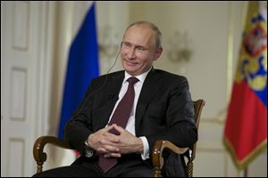 Russian President Vladimir Putin smiles during an interview with John Daniszewski, the Associated Press's Senior Managing Editor for International News during an AP interview at Putin's Novo-Ogaryovo residence outside Moscow.