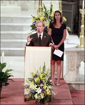 "John Patrick Gilligan, left, son of  Ohio Gov. John Joyce ""Jack"" Gilligan, gives the Eulogy while Gov. Gilligan's granddaughter Hannah Gilligan Commoss stands behind  during the memorial service."