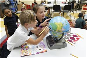 Kashayla Faulkner, left, watches Brittany Taber and Riley Taber find locations on a globe during the Toledo Public Schools/YMCA day-care program at DeVeaux Elementary School in West Toledo.