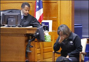 Judge Myron Duhart offers tissues to Keisha Boykin, 18, as she breaks down while testifying in the trial of Robert F. Carter. Carter is accused of killing her mother, Wendabi Triplett, 41.