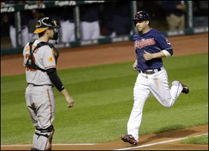Cleveland Indians' Jason Kipnis, right, scores on a sacrifice fly by Asdrubal Cabrera in the fourth inning of a baseball game, Tuesday, Sept. 3, 2013, in Cleveland. Baltimore Orioles catcher Matt Wieters is at left.