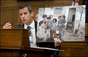 House Foreign Affairs Committee member Rep. Adam Kinzinger, R-Ill. holds up a photograph of Syrian children as he speaks on Capitol Hill in Washington, Wednesday, Sept. 4, 2013, during the committee's hearing on Syria.