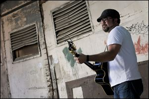 Toledo resident and local musician Jeff Stewart performs in an alley behind the Ye Olde Cock n Bull for a music video Wednesday in downtown Toledo.