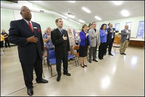 City Council Candidates from left, Larry Sykes, James P. Martin, Sandy Spang and Rob Ludeman stand for the Pledge of Allegiance with mayoral candidates Anita Lopez, Michael Konwinski and D. Michael Collins, right, during a candidate nights forum at the Friendship Park Community Center, in Point Place, Thursday.