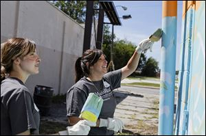 Abby Lewis of Perrysburg, right, paints with Danielle Scott of Maumee as they volunteer with others from MassMutual at the Munchie's Again building.