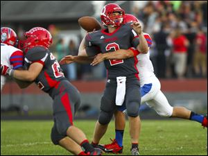 Bedford senior quarterback Brad Boss (2) is sacked by St. Francis senior David Nees (7).
