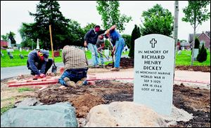 Workers from Landscape Design Inc., including from left, Matt Ackerman, Quincy Hens, Jeff Moritz (Landscape Design owner), Rick Ryan, and Dave Ferguson, install a commemorative garden around the new marker for Richard Dickey, who was lost at sea in World War II.