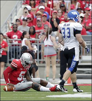 Braxton Miller, left, fights a leg cramp against Buffalo last week. Ohio State quarterbacks took six sacks during a season-opening victory last week. Only six of 120 FBS teams allowed more.