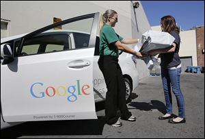 Google Shopping Express driver Ashley Beach, left, picks up packages from Sofe Ring, operations manager, in Palo Alto, Calif. Google has about 50 cars on the streets in an invitation-only experiment with a same-day delivery service.