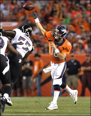 Denver Broncos quarterback Peyton Manning (18) throws under pressure from Baltimore Ravens outside linebacker Terrell Suggs (55) during the first half Thursday night in Denver.