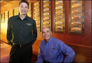 Jimmy Harmon, CEO of Tony Packo's, left, and Tony Packo, Jr., former owner and son of the company's founder, pose in front of hot dog buns signed by celebrities at the Front Street restaurant. Mr. Harmon has led Tony Packo's for 3½ months, taking over for Bob Bennett.