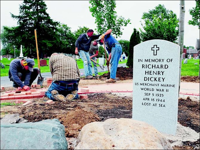 headstone1 Workers from Landscape Design Inc., including from left, Matt Ackerman, Quincy Hens, Jeff Moritz (Landscape Design owner), Rick Ryan, and Dave Ferguson, install a commemorative garden around the new marker for Richard Dickey, who was lost at sea in World War II.