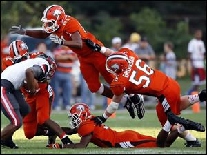 Sylvania Southview defenders Kal Aridi (21), Nate Hall (81), and Michael Bronson (56) bring down Central Catholic RB TreVon Wade (38).