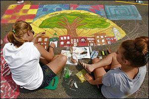 Eastwood High School art students Jenne Benier, 15, left, and Cassie VanDenk, 15, work on their team's creation for the festival's Chalk Walk contest. First prize is $500.