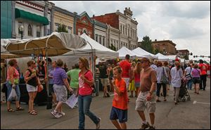 Hundreds of people mill around the artists' booths at the Black Swamp Arts Festival in downtown Bowling Green, which continues today from 11 a.m. to 5 p.m.