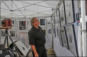 John Csomos of Maumee looks over the large format work of photographer J.D. Nolan at the annual Black Swamp Arts Festival in Bowling Green. The festival offered a mix of artists, from photographers to potters to glassmakers and more.