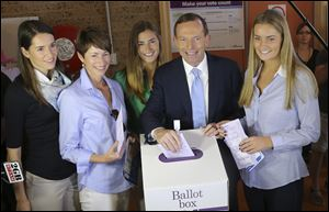 Australia's opposition leader Tony Abbott, second right, and his family from right, Bridget, Frances, wife Margaret and Louise cast their ballots today at Freshwater Surf Club in Sydney, Australia.