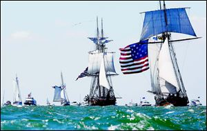 The Pride of Baltimore II, right, portraying the US Brig Caledonia, leads the US Brig Niagara through a flotilla of boats during the re-enactment of the Battle of Lake Erie.