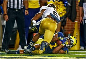 Michigan receiver Jeremy Gallon (21) scores a touchdown ahead of Notre Dame's KeiVarae Russell on a pass from Devin Gardner during the second quarter at Michigan Stadium.