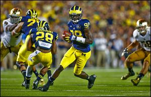 Michigan quarterback Devin Gardner rolls out during the second quarter against Notre Dame on Saturday in Ann Arbor. Gardner ran for one touchdown and passed for another. He will wear No. 98 for the remainder of the season, honoring 1940 Heisman Trophy winner Tom Harmon.