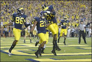 Michigan players, from left, Jehu Chesson, Jeremy Gallon, and A.J. Williams  celebrate one of Gallon's three touchdown catches against Notre Dame. He had eight catches for 184 yards.