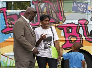 Toledo mayor Mike Bell talks to co-chair of the Warren Sherman community fest Peggy Brown, with her grandson Jermaine Williams, 5.