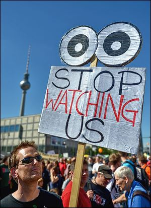 Activists  in Berlin protest on Saturday. A German weekly tells of NSA efforts to access phone data.