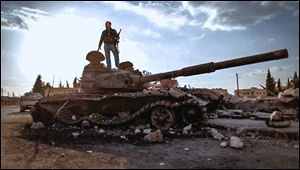 This citizen journalism image provided by the Syrian Revolution against Bashar Assad shows a Free Syrian army fighter standing on a damaged military tank in Zabadani, near Damascus on Sunday.